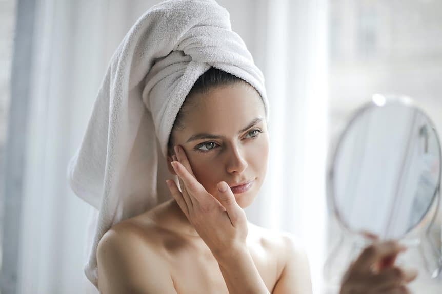 Woman in front of a mirror | Cosmetic Rejuvenation Center | Acne Treatment | Pepper Pike, OH